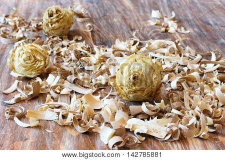 dry rosebuds in the sawdust on a wooden background