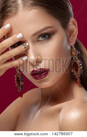 Glamorous portrait of a beautiful girl on a burgundy background jewelry crown professional make-up and hairstyle . The beauty of a clean face . Photographed in the studio.