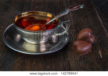 Black tea in vintage silver cup on an old wooden background