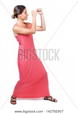skinny woman funny fights waving his arms and legs. Isolated over white background. A slender woman in a long red dress in boxing pose.