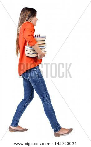 Girl comes with  stack of books. side view. Rear view people collection.  backside view of person.  Isolated over white background. girl in a red jacket with difficulty carries a lot of books under