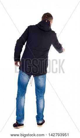 man in jacket holds out his hand for handshake. Rear view  people collection.  backside view of person.  Isolated over white background. A guy in a black jacket holding out his right hand in greeting.