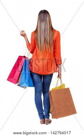 back view of woman with shopping bags. backside view of person.  Rear view people collection. Isolated over white background. girl in a red jacket holding a paper shopping bags.