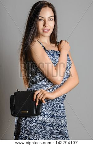 Cute brunette girl with long flowing hair holding a black handbag wearing a sundress with ornament