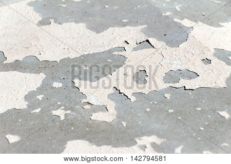 Stone colored old and cracked paint. Foreground and background are blurred.