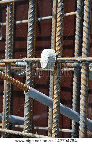 SELANGOR, MALAYSIA -SEPTEMBER 19, 2015: Hot rolled deformed steel bars or steel reinforcement bar and the concrete spacer. The spacer used to created gap between reinforcement bar and the form work.