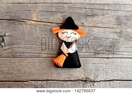 Halloween cute felt witch with broom on old wooden background. Halloween little witch ornament crafts for kids. Handicraft felt decor. Tutorial. Step. Top view