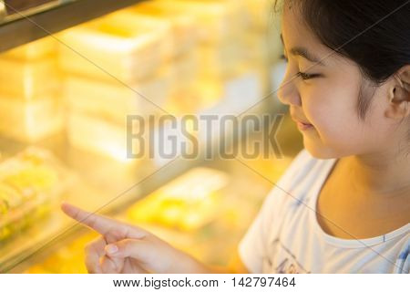 Asian girl looking and pointing at display window with different cakes