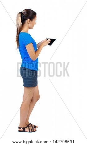 back view of standing young beautiful  woman using a mobile phone or tablet computer. girl  watching. Rear view people collection.  backside view of person.  Isolated over white background. girl in a