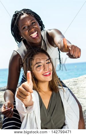 Close up portrait attractive young african girl doing thumbs up with white friend outdoors.
