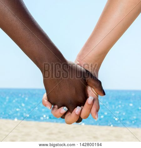 Macro close up of diverse female hands holding each other outdoors.