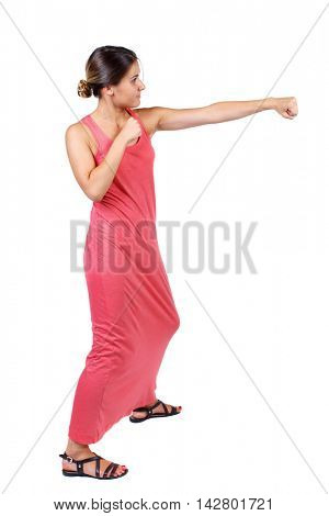 skinny woman funny fights waving his arms and legs. Isolated over white background. A slender woman in a long red dress fulfills hands.