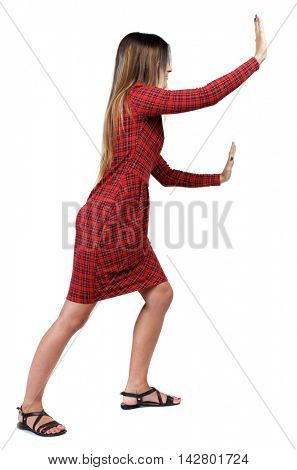 back view of woman pushes wall.  Isolated over white background. Rear view people collection. backside view of person. The girl in red plaid dress that pushes it ahead.