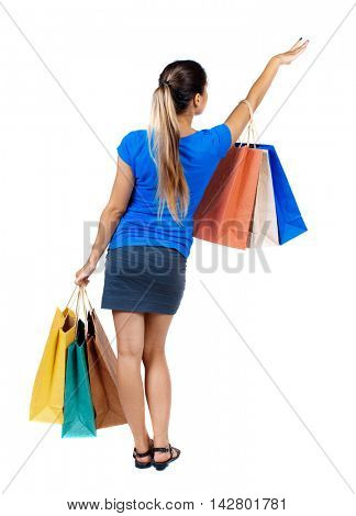 back view of woman with shopping bags. backside view of person.  Rear view people collection. Isolated over white background. girl in a short skirt and a blue shirt holding paper bags and points hand
