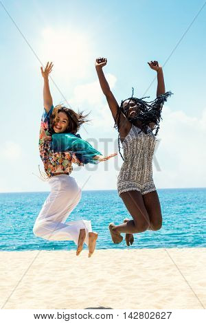 Full length action portrait of black and white women laughing and jumping together on beach.