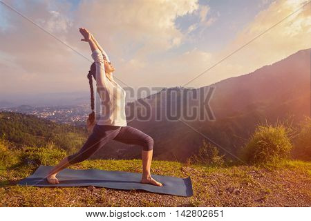Yoga outdoors - sporty fit woman doing yoga asana Virabhadrasana 1 - Warrior pose posture outdoors in Himalayas mountains in the morning