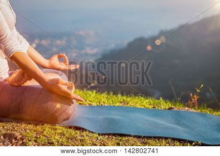 Close up of woman in Padmasana yoga lotus pose with chin mudra outdoors with copyspace. With light leak and lens flare