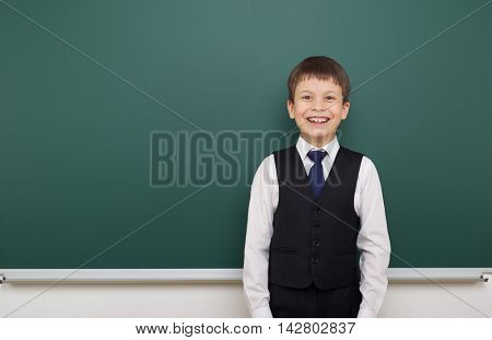 school student boy posing at the clean blackboard, grimacing and emotions, dressed in a black suit, education concept, studio photo