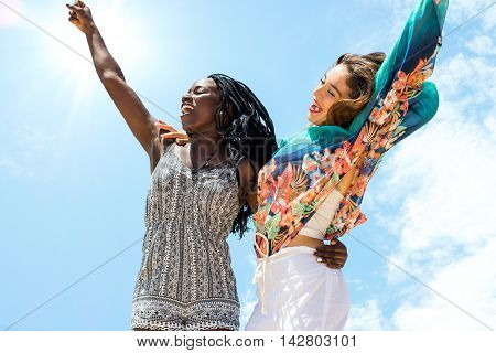 Close up action shot of young african woman jumping together with caucasian girlfriend against blue sky.