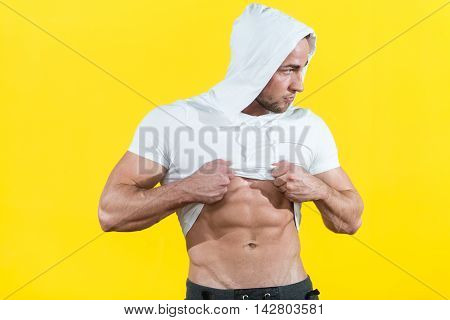 Healthy Young Man Flexing Muscles On Yellow Background