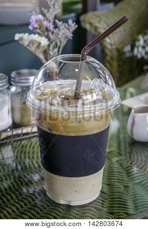 Iced coffee espresso in plastic cup for takeaway on the table