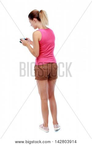 back view of standing young beautiful  woman  and using a mobile phone. girl  watching. Rear view people collection.  backside view of person.  Isolated over white background. Sport blond in brown
