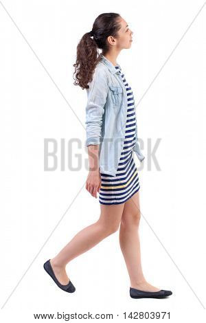 back view of walking  curly woman.  backside view of person.  Rear view people collection. Isolated over white background. Swarthy girl in a checkered dress goes to the side and looking up.
