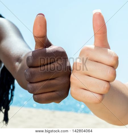 Macro close up of two diverse female hands doing thumbs up outdoors.
