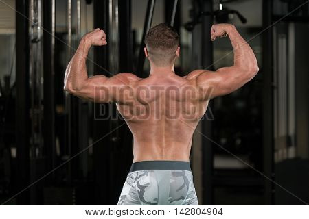 Muscular Man Flexing Muscles Rear Double Biceps Pose