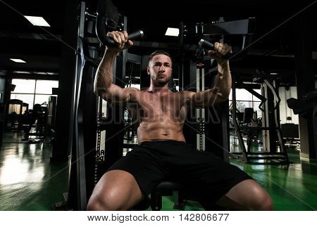 Young Man Exercise Chest On Machine