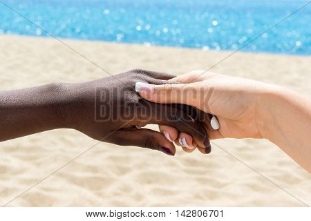 Macro close up of young white female hand holding african female hand outdoors.