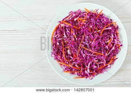 Salad coleslaw - red cabbage with carrots on white dish on white background authentic classic recipe view from above