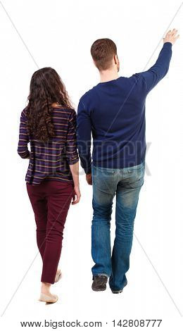 Back view of walking young couple (man and woman) pointing. Rear view people collection. backside view of person. Isolated over white background. Swarthy girl and the bearded man on the move shows his