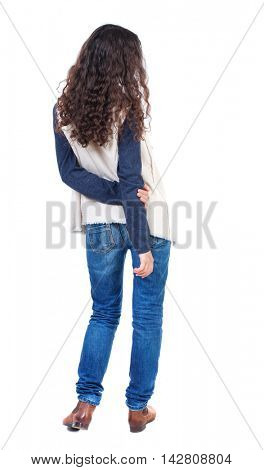 back view of standing young beautiful  woman.  girl  watching. Rear view people collection.  backside view of person. Long-haired girl with curly hair standing with his hands behind his back.
