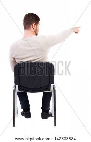 back view of young business man sitting on chair and pointing. Rear view people collection. The bearded man in a white warm sweater sits on a chair pointing sideways.