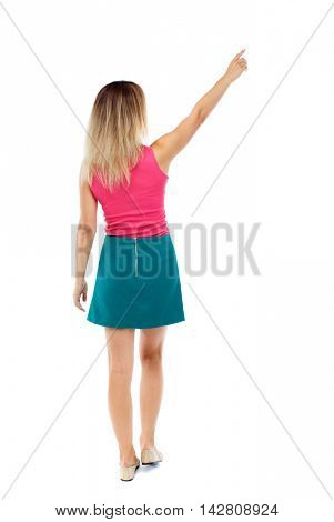 Back view of  pointing woman. beautiful girl. Rear view people collection.  backside view of person.  Isolated over white background. Blonde in a red sweater and green skirt went off pointing to the