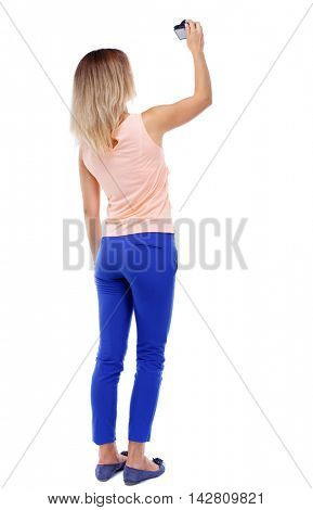 back view of standing young beautiful  woman  and using a mobile phone. girl  watching. Rear view people collection.  backside view of person.  Isolated over white background. The blonde in a pink t