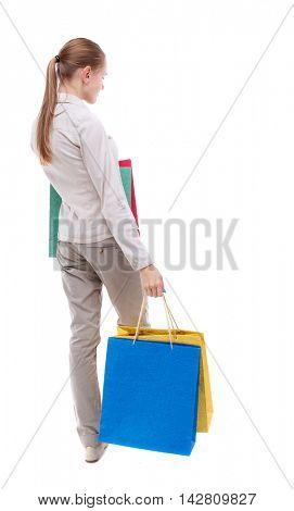 back view of woman with shopping bags. backside view of person.  Rear view people collection. Isolated over white background. Skinny girl in white denim suit standing with paper bags.
