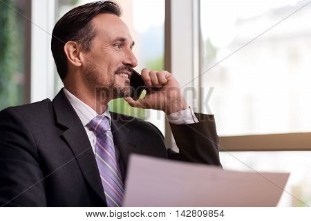 Glad to hear you. Cheerful delighted man smiling and looking aside while talking on cell phone
