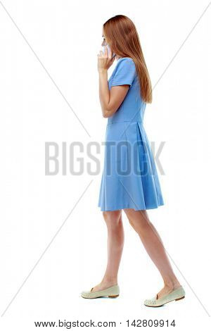 side view of a woman walking with a mobile phone. beautiful girl in motion.  backside view of person.  Rear view people collection. Isolated over white background. blonde in a blue dress while walking