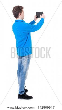 back view of standing business man photographing a phone or tablet. Rear view people collection.  backside view of person.  Isolated over white background. Curly boy in the blue jacket pictures of the