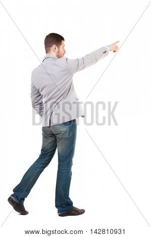 Back view of going  business man pointing. walking young guy . Rear view people collection.  backside view of person.  Isolated over white background. A man in a gray jacket is pointing in front of