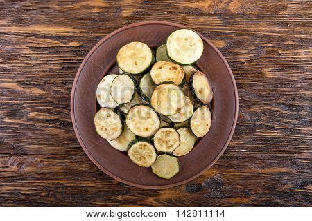 Fried zucchini in a clay plate on a wooden table. top view