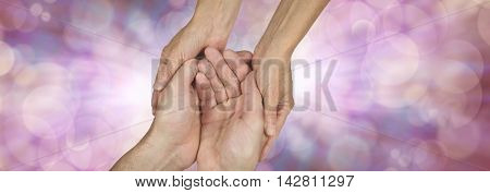 Compassionate Carer Banner -  wide banner with a woman's hands holding a man's cupped hands in a needy gesture on a pink bokeh and light burst background with plenty of copy space either side