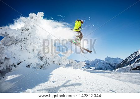 Skier at jump in Alpine mountains in beautiful sunny day. Copy-space for text