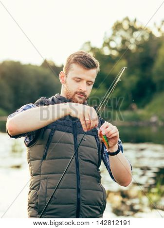Fisherman with a spinning rod and bait (lure, wobbler)  catching fish on a river. Man on a weekend. Hobby, leisure, active summer and autumn concept. Nature background.