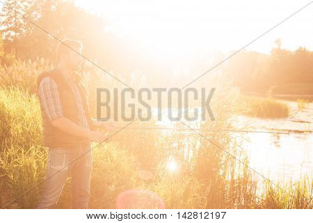 Fisherman with a spinning rod catching fish on a river. Man on a weekend. Hobby, leisure and active summer and autumn concept. Rural background.