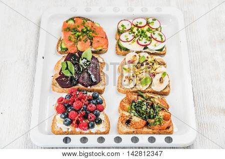 Sweet and savory breakfast toasts variety. Sandwiches with fruit, vegetables, eggs and smoked salmon on white baking tray over white painted wooden background, top view, selective focus