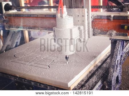 Milling machine cut out from white material pattern closeup