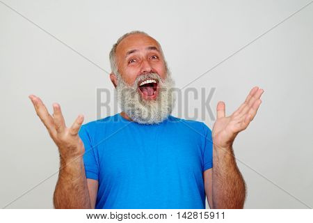 White-bearded senior male is posing at the camera gesturing happiness isolated against white background